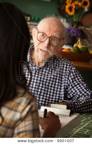 Elderly Man In Home With Care Provider Or Survey Taker