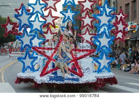 The Parade Queen And Her Attendants Ride On A Float