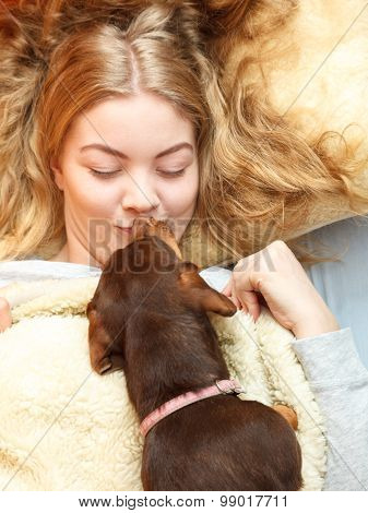 Woman kissing dog waking up in bed in the morning after sleeping. Young girl laying under wool blanket. poster