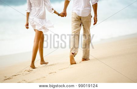 Back view of a couple taking a walk holding hands on the beach