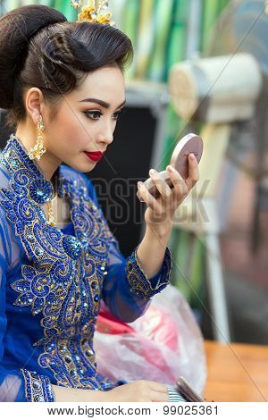 BANGKOK, THAILAND, February 17, 2015 : A Thai lady traditional dancer is checking her makeup before the show celebrating the new Krung Kasem floating market in the Thewet district of Bangkok, Thailand