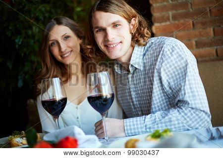 Young couple sitting in caf�© and having supper