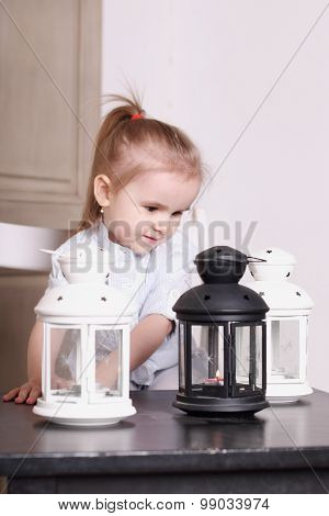 Cute Little Blond Girl Playing With Three Luminaires With Candle. Focus On Right Lamp. Shallow Dof