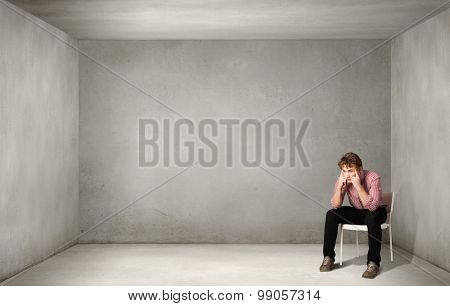 Depressed man sitting on a chair all alone