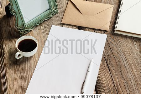 The mockup on wooden background with vintage old picture frame, pen, pencil, cup of coffee, white blank paper for writing, envelope and notebook poster