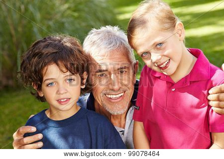 Grandfather with two happy grandkids in a green garden