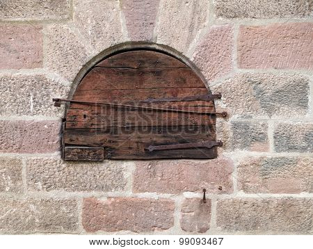 Round small wooden door in an old masonry