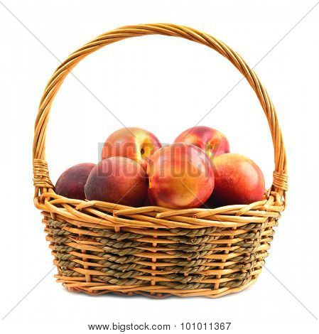 nectarines and peaches in basket isolated over white