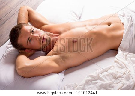 Attractive young man lying in bed
