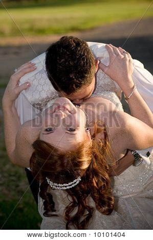 just married couple with groom kissing bride in the cleavage
