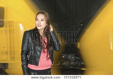 Woman standing in front of a passing train, trying to keep her hear from blowing in her face by the slipstream