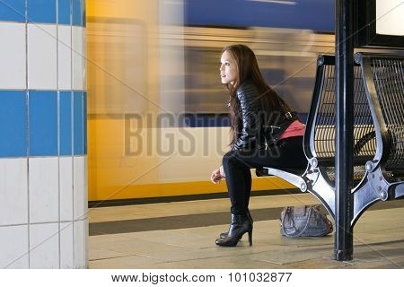 Woman, sitting on a bench, with her purse on the platform next to her, looking at a passing train, waiting.