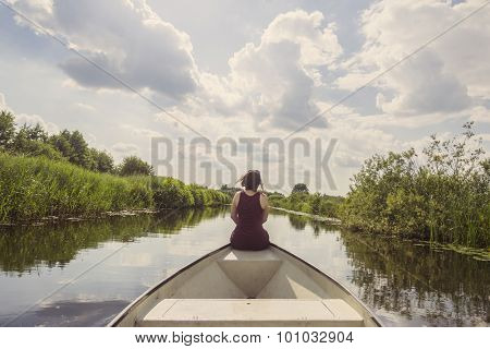 Young woman in a summer dress sitting on the bow of an electric whisperboat, enjoying a beautiful summer day with her feet overboard, gently sailing through a canal, surrounded by nature