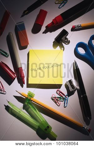 The word online education against students table with school supplies