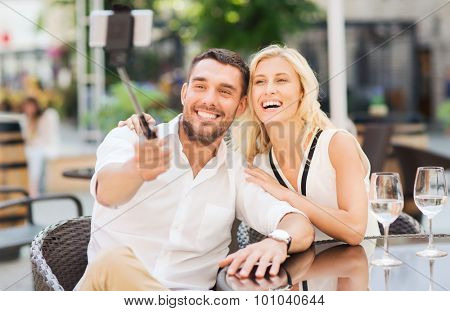 love, date, technology, people and relations concept - happy happy couple taking picture with smartphone on selfie stick at city street cafe or restaurant