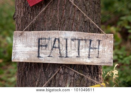 A wooden plaque with the word faith