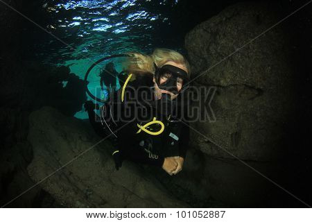 Beautiful blonde scuba diving instructor enters an underwater cave
