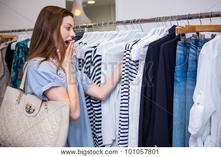 Brunette shocked by price of clothing in fashion boutique