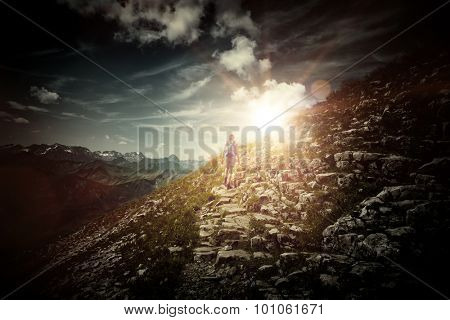 Rear View of Female Hiker Ascending Precarious Trail on Side of Rocky Mountain Heading Toward Bright Dramatic Sunlight with Vignette Effect - Concept Image Illustrating Inspiration and Aspiration