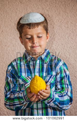 Etrog -  ritual fruit for the Jewish holiday of Sukkot. Beautiful seven year old boy in white knitted skullcap is holding citron