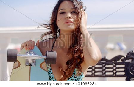 Sexy seductive young woman with long curly brown hair holding a skateboard looking at the camera with a sultry expression as she poses in front of the ocean on a beachfront promenade.