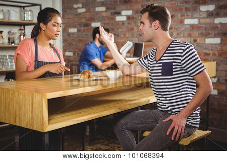 Unhappy customer complaining about the croissant in a cafe