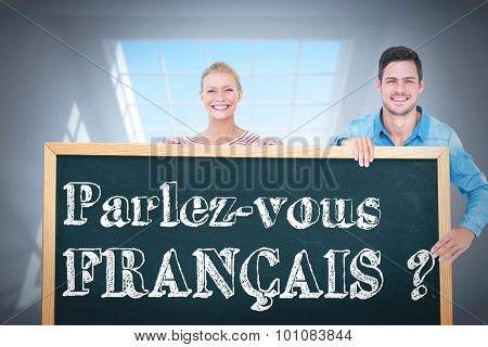 Happy man and woman pointing to card against room with large windows