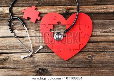 Red Puzzle Heart With Stethoscope On Brown Wooden Background