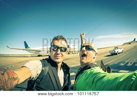 Modern hipster young friends taking a selfie at international airport - Adventure travel lifestyle enjoying moment and sharing happiness - Trip together around the world as alternative lifestyle poster