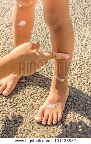 Sunblock Lotion Applied On Child Legs