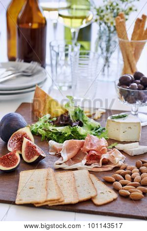 Selection of cheese and charcuterie with wine served as party snacks starters canapes poster