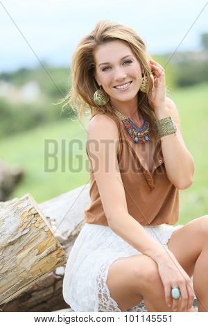 Attractive model woman sitting on old trunk