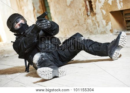 Military industry. Special forces or anti-terrorist police soldier,  private military contractor armed with pistol ready to attack lying on ground during clean-up operation, mission