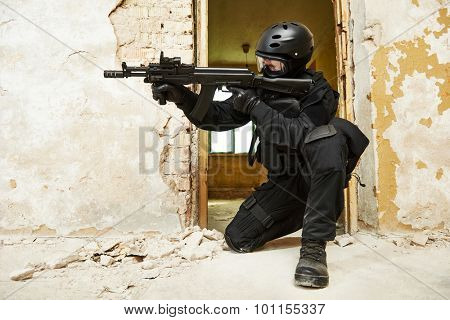 Military industry. Special forces or anti-terrorist police soldier,  private military contractor armed with assault rifle ready to attack during clean-up operation, mission poster