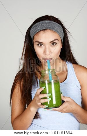 An athelte drinking a green shake after workout