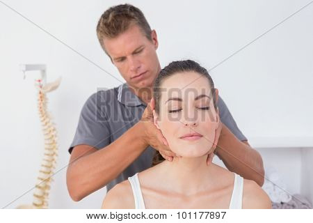 Doctor doing neck adjustment in medical office poster