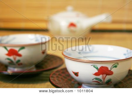 two typical japanese teacups and teapot on a tatami mat. this type of teapot is widely used to serve small amounts of tea as it holds only about two cups. poster