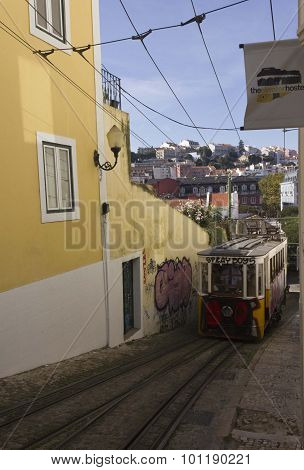 Lavra Funicular In The Narrow Street With Lisbon Skyline