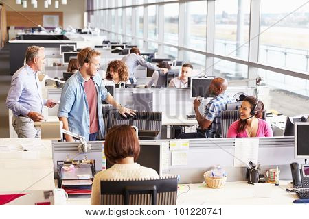 Casually dressed colleagues talking in an open plan office