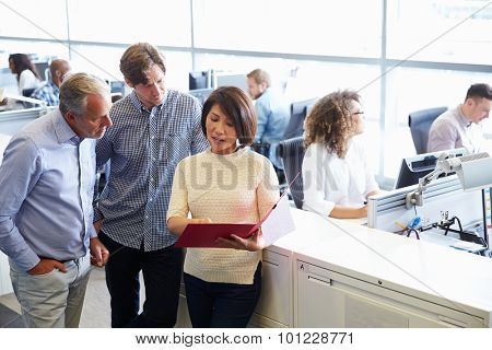 Casually dressed staff standing in a busy open plan office