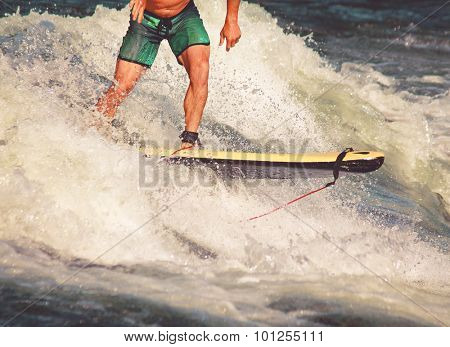 a surfer riding a wave in a full wet suit toned with a retro vintage instagram filter app or action effect (SHALLOW DOF action shot)