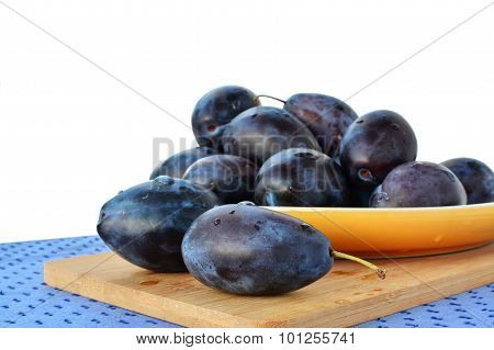 Damson Plums On Yellow Plate Over White