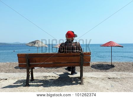 Elderly man sitting on a bench by the beach