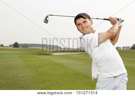 Golfer swinging his niblick out on the course