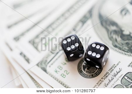 casino, gambling and fortune concept - close up of black dice and dollar cash money poster