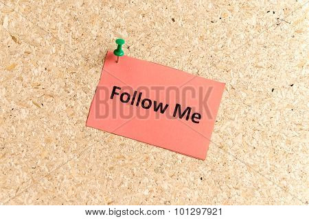 follow me word typed on a paper and pinned to a cork notice board poster