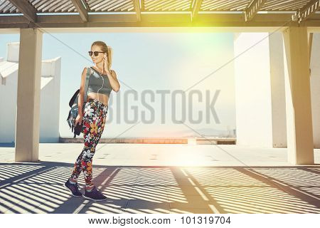 Young fitness blonde woman in sportswear listening music with headphones after training outdoors at beautiful sunny day. Girl runner enjoying sun and listen music in earphones from smartphone. poster
