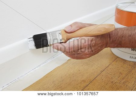 Close Up Of Man Painting Skirting Board