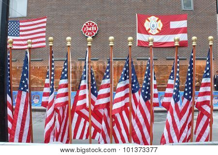 Array of US flags in front of memorial wall