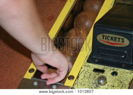 teenager reaching for a ball in skee ball. poster